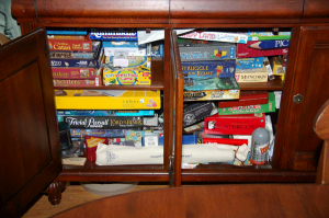 Many Board Games Taking Up a Cabinet